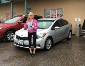 Jessica all smiles with her Kia Forte!