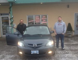 Retruning customer David and his son spencer picking up their 2008 Mazda 3