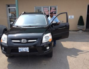 John eager to drive off with his 2010 Kia Sportage!